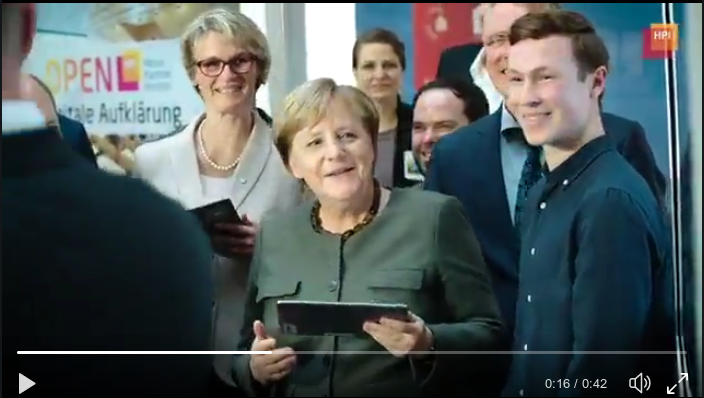 The image shows the German chancellor holding a tablet PC, surrounded by colleagues and others