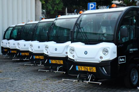 The image shows a row of parked electric street sweper cars, from the city of Porto