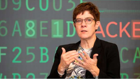 The image shows defence minister Annegret Kramp-Karrenbauer against a background of digital numbers and characters.